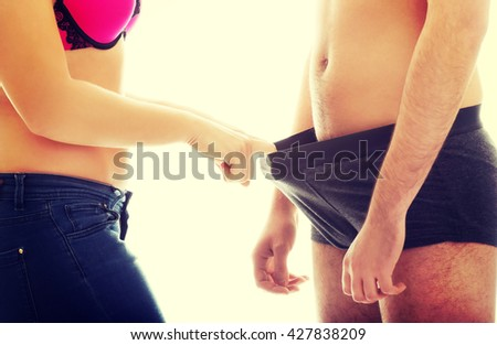 Attractive woman looking into man's panties. - stock photo