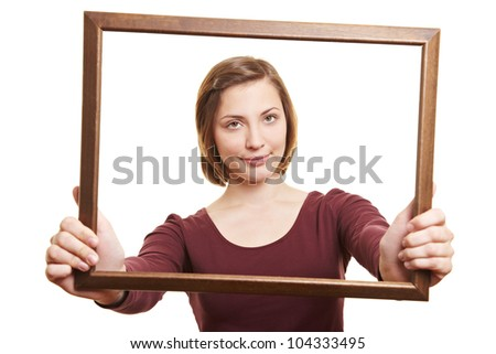 Attractive woman looking through empty wooden picture frame - stock photo