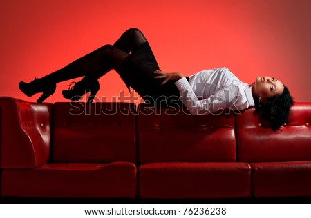 attractive woman lying down on a couch over red background