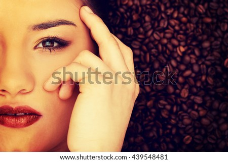 Attractive woman lying in coffee grains.  - stock photo