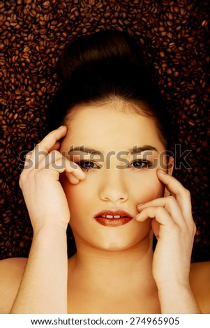 Attractive woman lying in coffee grains touching face. - stock photo