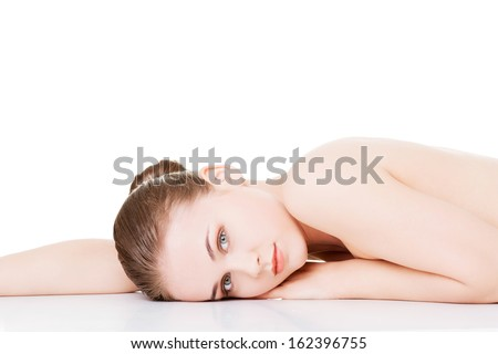 Attractive woman lying on the floor and looking at camera. Isolated on white.