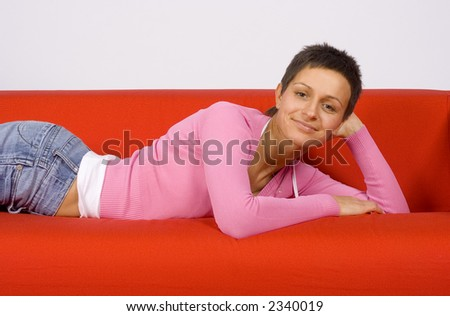 attractive woman lying on the red sofa - stock photo