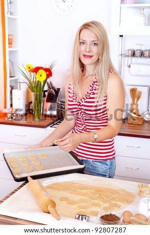 Attractive woman making cookies in the kitchen - stock photo