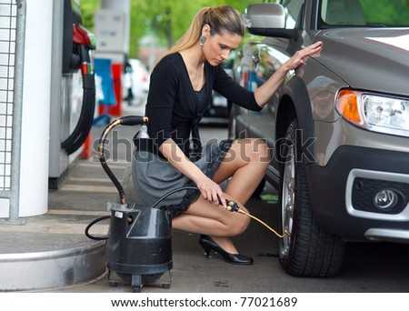 attractive  woman measuring pressure in car tire at gas station