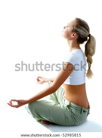 Attractive woman meditating in pose of lotus and looking at light - stock photo
