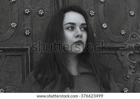 Attractive woman near an old door. Black and white shot