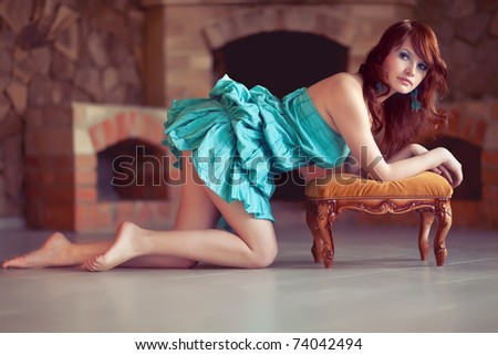 Attractive woman near the fireplace - stock photo