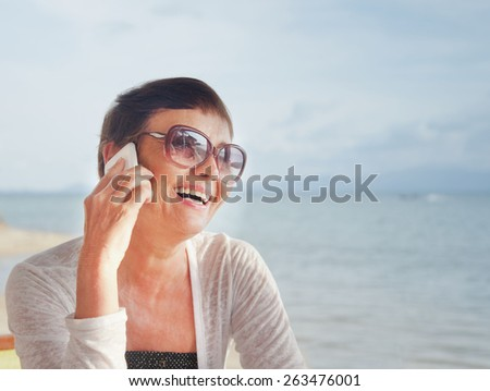 attractive woman of 50 years with a mobile phone at the beach cafe on the background of the sea - stock photo