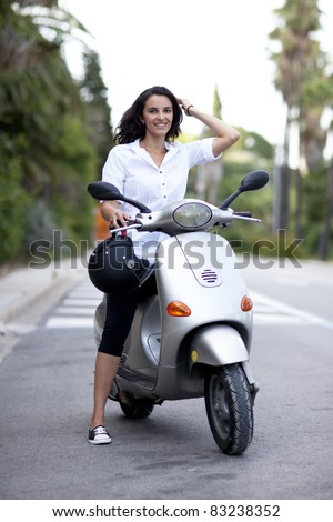 Attractive woman on a scooter - stock photo
