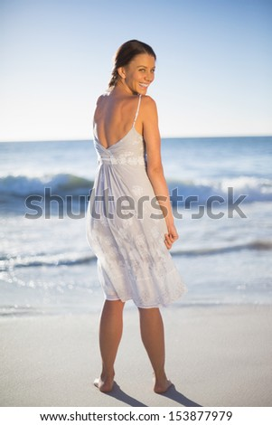 Attractive woman on the beach looking over shoulder at camera
