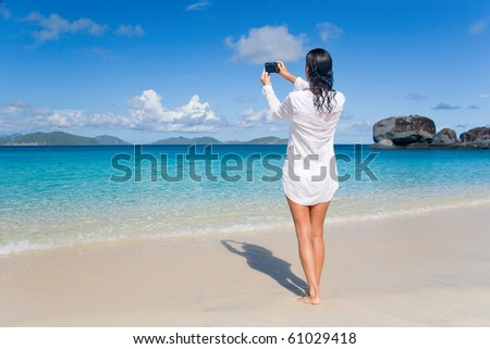 attractive woman on tropical beach taking photo with camera - stock photo