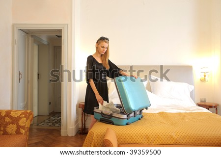 attractive woman opening suitcase in a hotel room - stock photo