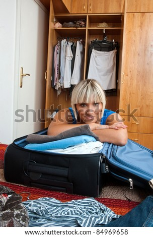 attractive woman packing clothes in luggage in her bedroom - stock photo