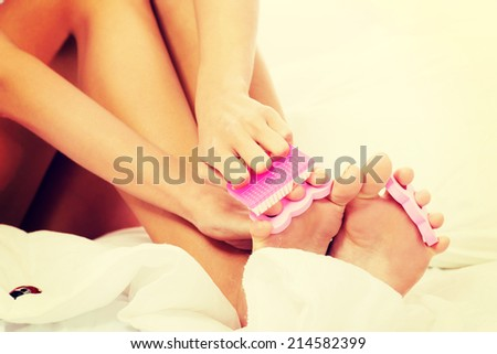 Attractive woman painting her toes in bed. Over white background. - stock photo