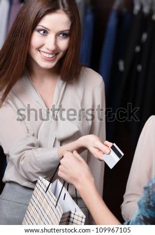 Attractive woman pays with credit card at the store - stock photo