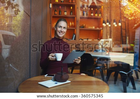 Attractive woman photographed through the window of modern cafe which sitting at the table with cup of tea and working on touch pad, beautiful female viewing news on digital tablet during work break - stock photo
