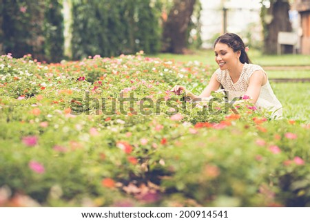Attractive woman picking flowers in the garden, selective focus - stock photo