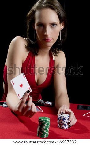 Attractive woman playing poker at a red poker table wearing red dress - stock photo