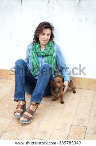 Attractive woman playing with dachshund dog