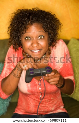 Attractive woman plays video game with hand held controller - stock photo