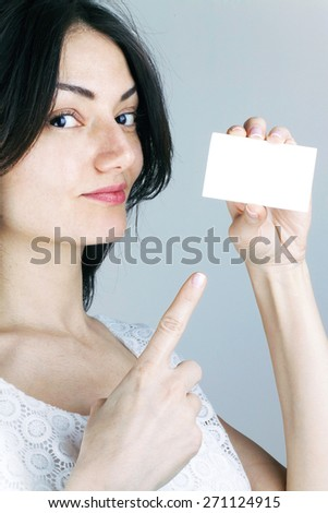 Attractive Woman Pointing Empty White Business Card Paper - stock photo