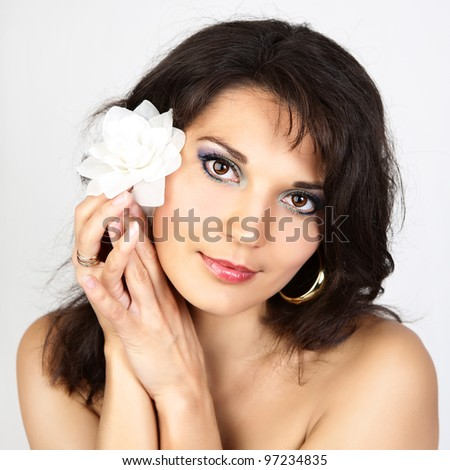 Attractive woman portrait with white flower on grey background.