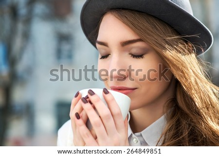 attractive woman poses with white cup. happy smile girl drink smells coffee or tea. city background - stock photo