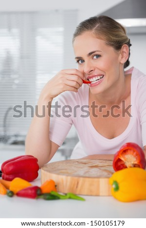 Attractive woman posing while eating vegetables in the kitchen