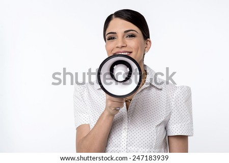 Attractive woman proclaiming into megaphone - stock photo