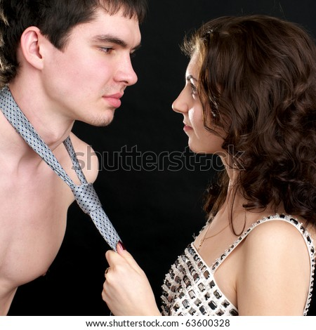 Attractive woman pulls naked man by a necktie - stock photo