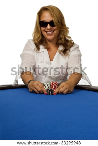 Attractive woman pushes her poker chips forward on a blue felt poker table. - stock photo