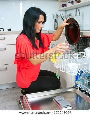 attractive woman putting dishes in dishwasher