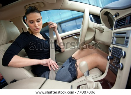 attractive woman putting on safety belt in her car