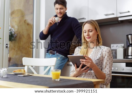 Attractive woman reading a tablet computer as she sits at a table in the kitchen watched by her husband drinking coffee behind - stock photo