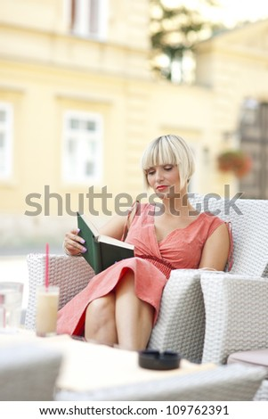 attractive woman reading book in the cafe - stock photo