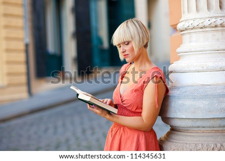 attractive woman reading book on the street corner - stock photo