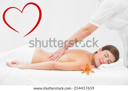 Attractive woman receiving back massage at spa center against heart - stock photo