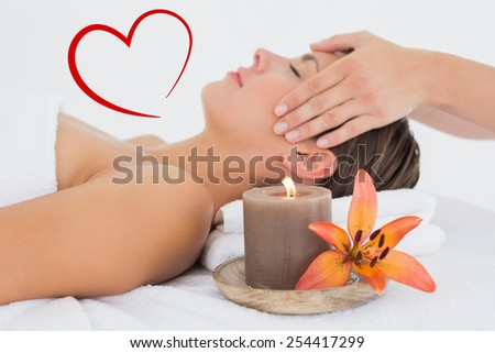 Attractive woman receiving head massage at spa center against heart - stock photo