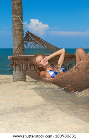 Attractive woman reclining in a hammock strung from a palm enjoying the tranquillity of a tropical beach - stock photo