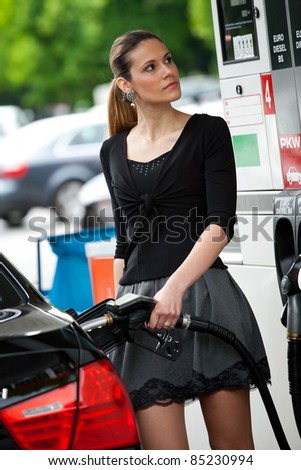 attractive woman refuel car at gas station - stock photo