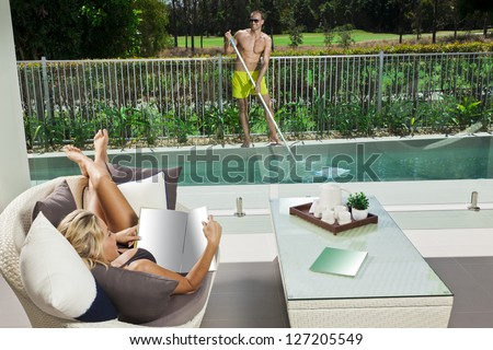 Attractive woman relaxing in backyard patio with pool boy cleaning the pool - stock photo
