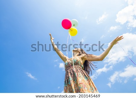 Attractive woman releasing balloons in the sky - Freedom,happiness,summer concept - stock photo