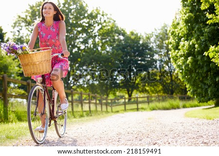 Attractive Woman Riding Bike Along Country Lane - stock photo