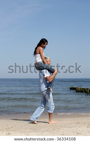 Attractive woman riding on man's shoulders on the beach