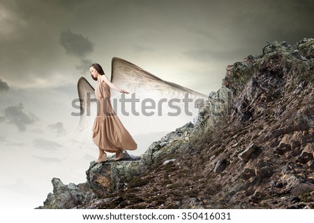 Attractive woman running with angel wings behind back