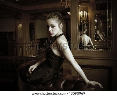 attractive woman seated in a luxury living room - stock photo