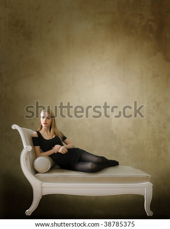 attractive woman seated on a chaise-longue - stock photo