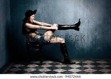 attractive woman sit in old grunge room pull on boots, full body shot