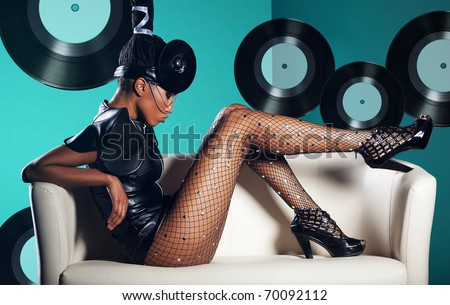 Attractive woman siting in white chair on records background - stock photo